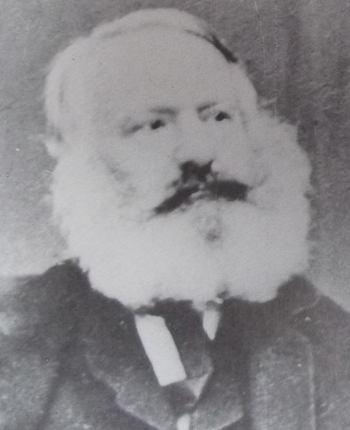 Portrait photographique de Victor Hugo, en 1864, regardant de côté, avec une barbe blanche très fournie et une moustache sombre.