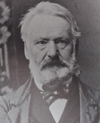 Portrait photographique de Victor Hugo, en 1867, face à l'objectif, le regard légérement de côté, les cheveux courts, la barbe taillée, le col agrémenté d'un noeud papillon.