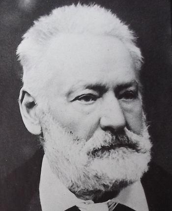 Portrait photographique de Victor Hugo, en 1877, le visage tourné sur le côté, les cheveux en brosse, la barbe et la moustaches taillées, le regard triste.