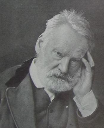 Portrait photographique de Victor Hugo, en 1879, le visage posé sur sa main gauche, les cheveux courts ébouriffés, barbe et moustaches taillées, le regard fatigué.