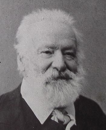 Portrait photographique de Victor Hugo, en 1884, les yeux rieurs, dirigés sur la droite. Sa barbe lui fait comme un halo.